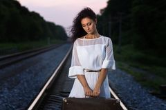 Young beautiful sad woman with suitcase at the railroad Royalty Free Stock Photography