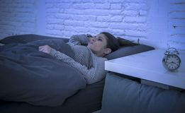 Young beautiful sad and worried latin woman suffering insomnia and sleeping disorder problem unable to sleep late at night lying o. N bed awake feeling stressed Royalty Free Stock Photo