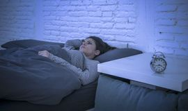 Young beautiful sad and worried latin woman suffering insomnia and sleeping disorder problem unable to sleep late at night lying o. N bed awake feeling stressed Royalty Free Stock Image
