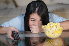 Young beautiful and scared Asian Korean teenager woman in fear watching horror scary movie at home sofa couch eating popcorn bowl royalty free stock photography