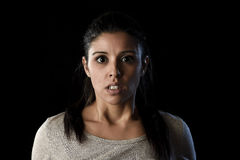 Young beautiful scared Spanish woman in shock and surprise face expression isolated on black. Young beautiful scared Spanish woman in shock and surprise face Stock Image
