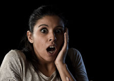 Young beautiful scared Spanish woman in shock and surprise face expression isolated on black. Young beautiful scared Spanish woman in shock and surprise face Stock Images