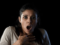 Young beautiful scared Spanish woman in shock and surprise face expression isolated on black. Young beautiful scared Spanish woman in shock and surprise face Stock Photo