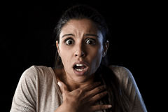 Young beautiful scared Spanish woman in shock and surprise face expression isolated on black. Young beautiful scared Spanish woman in shock and surprise face Royalty Free Stock Photos