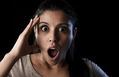 Young beautiful scared Spanish woman in shock and surprise face expression isolated on black. Young beautiful scared Spanish woman in shock and surprise face Royalty Free Stock Image