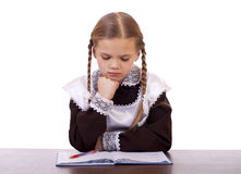 Young beautiful schoolgirl sitting at a desk Stock Images