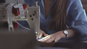 Young beautiful seamstress diligently working at the sewing machine. stock footage