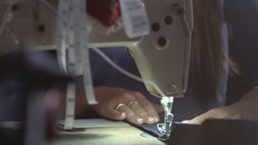 Young beautiful seamstress diligently working at the sewing machine. stock video