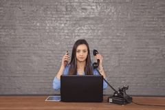 Young beautiful secretary to conduct two phone calls at one time. The concept of task-oriented stock photos