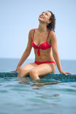 Young beautiful sexual woman sitting on ledge pool. On resort against sea Royalty Free Stock Images