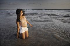 Young beautiful asian woman smiling free and happy having fun at sunset beach in Bali island of Indonesia kneeling on sand Stock Images
