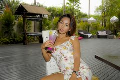 Young beautiful and sexy Asian woman in stylish dress at holiday resort coffee shop or restaurant drinking healthy fruit juice. Outdoors in relax and lifestyle Royalty Free Stock Photo