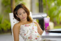 Young beautiful and Asian woman in stylish dress at holiday resort coffee shop or restaurant drinking healthy fruit juice royalty free stock photos