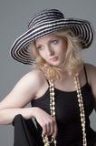 Young beautiful sexy  blonde woman. Young beautiful  blonde woman in a hat and a black dress sitting on a chair,dreaming and posing for the camera close-up Royalty Free Stock Photo