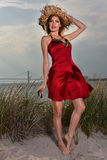 Young beautiful sexy blonde woman wearing straw hat and elegant red dress posing on the beach. Royalty Free Stock Image