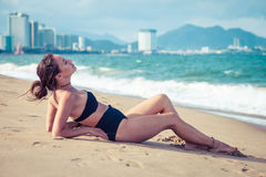 Young beautiful sexy brunette bikini model laying on sea beach. Exotic country travel and rest concept. Royalty Free Stock Photo