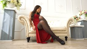 Young beautiful sexy brunette girl in a red dress sitting on the couch in the luxury interior stock video footage