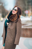 Young beautiful sexy brunette girl, woman with chic long dark hair in stylish sunglasses, elegant fur coat with fur and Royalty Free Stock Image