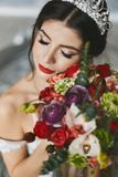 Young beautiful and brunette woman, in white dress and diadem on her head, with flowers in her hands stock image