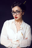 Young beautiful business lady with updo hair wearing white silk blouse and trendy glasses royalty free stock photography