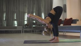 Young beautiful sporty Caucasian girl exercising yoga positions, asana. Indoors. stock video