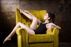 A young beautiful, Caucasian woman with thin figure and long bare legs, barefoot posing reclining on yellow armchair in the i royalty free stock photography