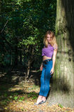 Young beautiful sexy girl blond model with long blond hair in jeans and jacket posing in the woods among the trees and vegetation Stock Photos