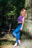 Young beautiful sexy girl blond model with long blond hair in jeans and jacket posing in the woods among the trees and vegetation Royalty Free Stock Image
