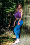 Young beautiful sexy girl blond model with long blond hair in jeans and jacket posing in the woods among the trees and vegetation Royalty Free Stock Photos