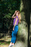 Young beautiful sexy girl blond model with long blond hair in jeans and jacket posing in the woods among the trees and vegetation Royalty Free Stock Photography