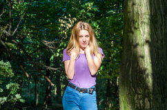 Young beautiful sexy girl blond model with long blond hair in jeans and jacket posing in the woods among the trees and vegetation Stock Photo