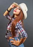Young beautiful girl in cowboy hat. On grey background Stock Photos
