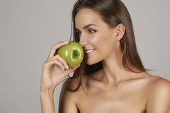 Young beautiful girl with dark curly hair, bare shoulders and neck, holding big green apple to enjoy the taste and are dietin Royalty Free Stock Photos