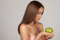 Young beautiful sexy girl with dark curly hair, bare shoulders and neck, holding big green apple to enjoy the taste and are dietin Royalty Free Stock Photo