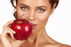 Young beautiful sexy girl with dark curly hair, bare shoulders and neck, holding big red apple to enjoy the taste and are dieting,. Healthy eating organic foods Stock Images