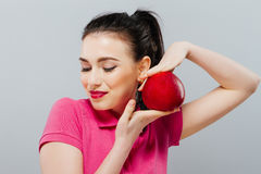 Young beautiful girl with dark curly hair, bare shoulders and neck, holding big red apple to enjoy the taste and royalty free stock photos