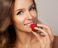 Young beautiful sexy girl with dark curly hair, bare shoulders and neck, holding strawberry to enjoy the taste and are dieting,. Healthy eating organic foods Stock Photos