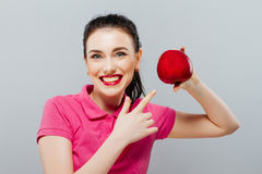 Young beautiful girl with dark hair, holding big red apple to enjoy the taste and are dieting, healthy eating and stock image
