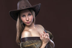 Young beautiful girl in fur waistcoat and cowboy hat. Young beautiful girl in fur waistcoat and a cowboy hat on brown background stock photos