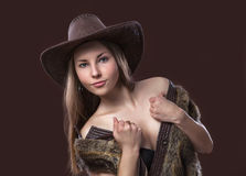 Young beautiful girl in fur waistcoat and cowboy hat. On a brown background stock images