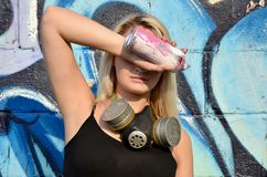 Young and beautiful girl graffiti artist with gas mask on her neck hiding his eyes with a spray can. Standing on a wall background with a graffiti pattern in royalty free stock photos