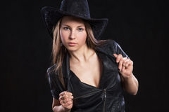 Young beautiful girl leather jacket and black cowboy hat. On black background royalty free stock image