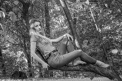 Young beautiful sexy girl model of European appearance with long hair in a shirt and jeans sitting on a tree during a walk in the Stock Photo
