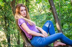 Young beautiful sexy girl model of European appearance with long hair in a shirt and jeans sitting on a tree during a walk in the Royalty Free Stock Images