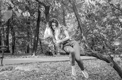 Young beautiful sexy girl model of European appearance with long hair in a shirt and jeans sitting on a tree during a walk in the Royalty Free Stock Photo
