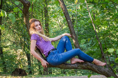 Young beautiful sexy girl model of European appearance with long hair in a shirt and jeans sitting on a tree during a walk in the Stock Photos