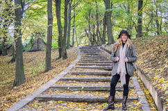 Young beautiful sexy girl model posing in the autumn park among fallen yellow leaves on the old stairs in a hat, coat, jeans and b Royalty Free Stock Images