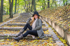 Young beautiful sexy girl model posing in the autumn park among fallen yellow leaves on the old stairs in a hat, coat, jeans and b Stock Images