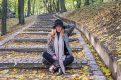 Young beautiful sexy girl model posing in the autumn park among fallen yellow leaves on the old stairs in a hat, coat, jeans and b Royalty Free Stock Image