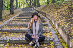 Young beautiful sexy girl model posing in the autumn park among fallen yellow leaves on the old stairs in a hat, coat, jeans and b Stock Image